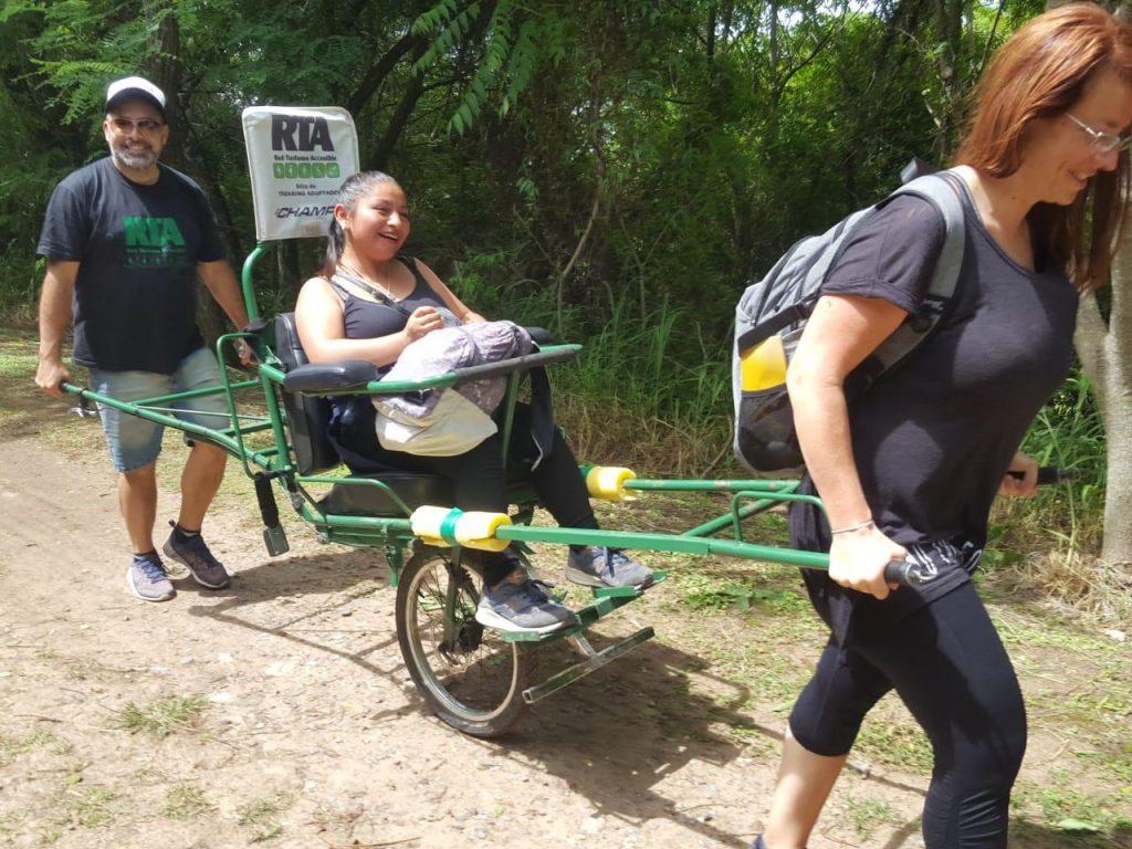 Mujer con discapacidad motriz llevada en silla de ruedas adaptada